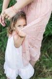 女儿拥抱母亲,在花的家庭photosession 免版税库存图片