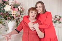女儿拥抱站立在她后的成熟母亲 库存照片