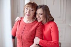 女儿拥抱站立在她后的成熟母亲 库存图片