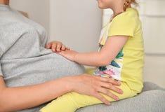 女儿接触一个怀孕的母亲的腹部 库存照片