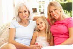 女儿放松孙女的祖母 免版税库存图片