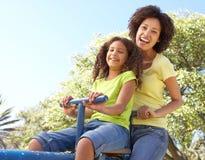 女儿母亲公园骑马跷跷板 免版税图库摄影