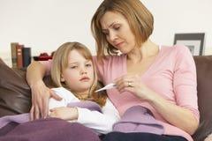 女儿母亲病态的采取的温度 免版税库存图片