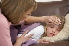 女儿母亲病态的采取的温度 图库摄影
