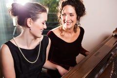 女儿母亲钢琴使用 免版税库存图片