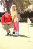 女儿父亲教的高尔夫球作用 免版税库存照片