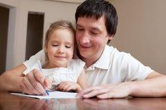 女儿生帮助的家庭作业 免版税库存照片