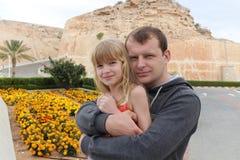 女儿穿戴了容忍父亲山雪板运动立场诉讼顶层 免版税库存照片