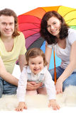 女儿系列坐的伞下 免版税库存图片