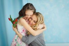 女儿给了她的母亲郁金香花束  免版税库存照片