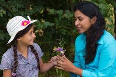 女儿给花她的母亲 免版税图库摄影