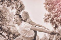 给女儿肩扛的父亲在公园 免版税库存图片