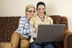 女儿膝上型计算机母亲使用 免版税图库摄影