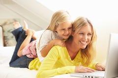 女儿膝上型计算机母亲松弛沙发使用 免版税库存图片