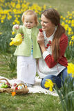 女儿装饰了复活节彩蛋母亲 免版税图库摄影