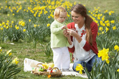 女儿装饰了复活节彩蛋母亲 库存图片