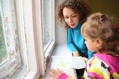 女儿近历史记录母亲读了视窗 免版税库存照片