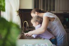 女儿以她的洗他们的在厨房水槽的手的母亲 免版税库存照片