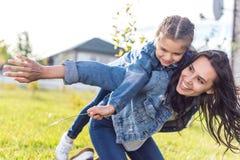 女儿biggyback户外骑马母亲在晴朗 免版税图库摄影