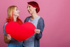 女同性恋者在桃红色背景拿着心脏并且看彼此 免版税库存照片