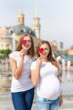 女同性恋者母亲,怀孕的夫妇,愉快的同性家庭在城市公园在夏天 拿着甜点的妇女,心形 免版税图库摄影