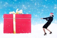女商人下拉式与链子的圣诞节礼品 免版税库存照片