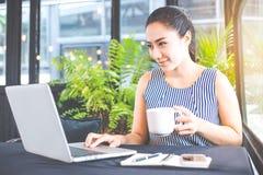 女商人与一台便携式计算机一起使用在办公室 免版税库存图片