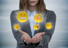 女商人与实施和与火光的emojis反对灰色木盘区 库存例证