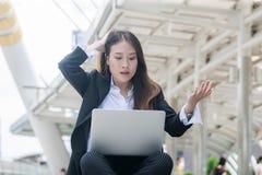 年轻女商人与看有震惊消极重音姿势的膝上型计算机一起使用膝上型计算机笔记本 免版税库存图片