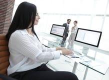 女商人与财政图一起使用在一个现代办公室 库存照片