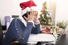 女商人以圣诞老人在书桌办公室的帽子宿酒 免版税库存照片