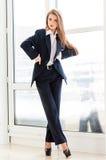 年轻女商人佩带的人的衣服和高跟鞋在办公室 免版税库存图片