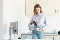 女商人倾吐从水壶的水 一在顶楼样式的办公室 免版税库存照片
