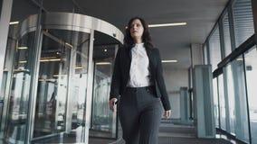 女商人出口通过一个现代商业中心的循环活动 西装的女孩看手表 股票视频