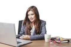 年轻女商人可爱与在桌上的膝上型计算机 库存照片