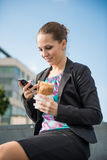 女商人吃和与电话一起使用 库存图片