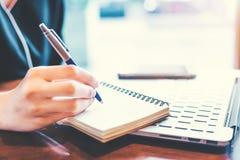 女商人在一个笔记薄的手文字与一支笔在办公室 免版税库存照片