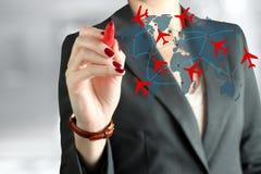 年轻女商人在世界地图的画的飞机路线 免版税图库摄影