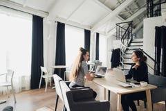 女商人在会议谈论在现代办公室 坐在与膝上型计算机的同一张桌上的两个女性工友 图库摄影