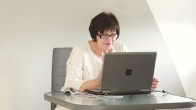女商人在办公室在工作 小心地看在玻璃的膝上型计算机屏幕 企业夫人微笑 影视素材