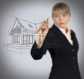 女商人在屏幕上的图画房子 免版税库存照片