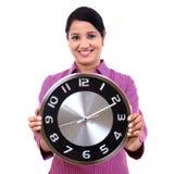 年轻女商人在手上的拿着时钟 图库摄影