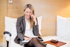女商人在旅馆客房谈话在电话,当在商务旅游时 库存照片