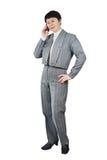 女商人在灰色诉讼谈话穿戴了由移动电话 库存照片