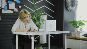 女商人在贴纸写下某事,当坐在桌上时 股票视频