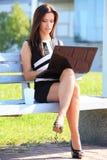 年轻女商人坐公园长椅 免版税库存照片