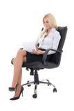 女商人坐办公室椅子和与膝上型计算机一起使用我 免版税库存图片