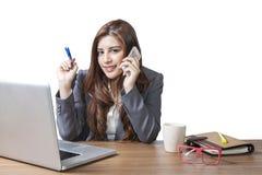 女商人坐在办公桌和谈话在手机 免版税库存照片