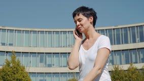 女商人坐在办公楼前面和谈话在电话 股票录像