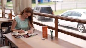 女商人坐在咖啡馆的一张桌上并且做在笔记本的笔记 股票录像
